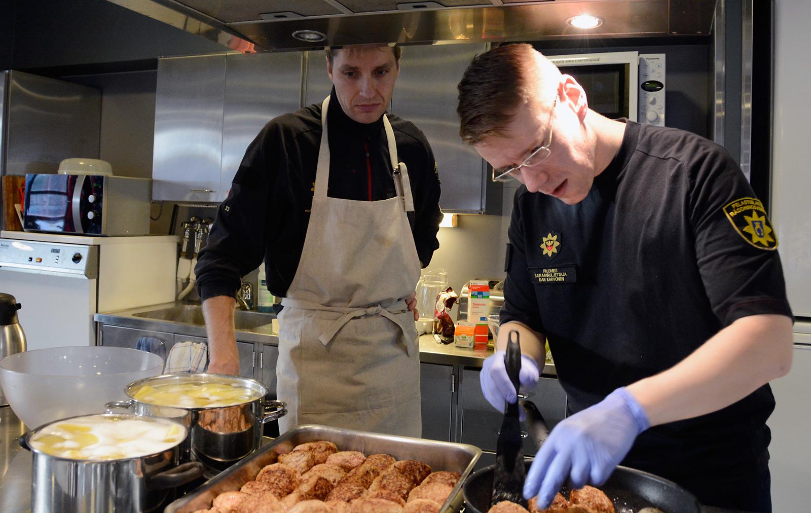 Palomies-sairaankuljettajat Ilari Vehviläinen (vas.) ja Dan Karvonen valmistavat legendaarisia Niittykummun paloaseman nelosvuoron lauantailihapullia.