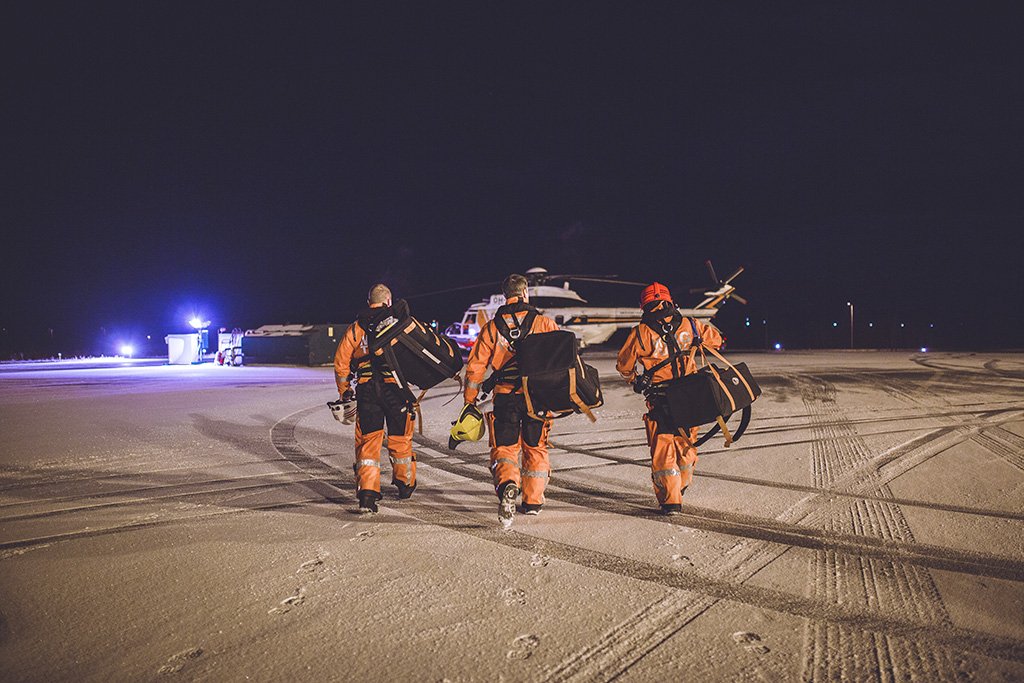 Marko Virolainen, Juha Oksa ja Risto Kemppainen kävelevät kohti helikopteria vartiolentueen kentällä Kärsämäellä.
