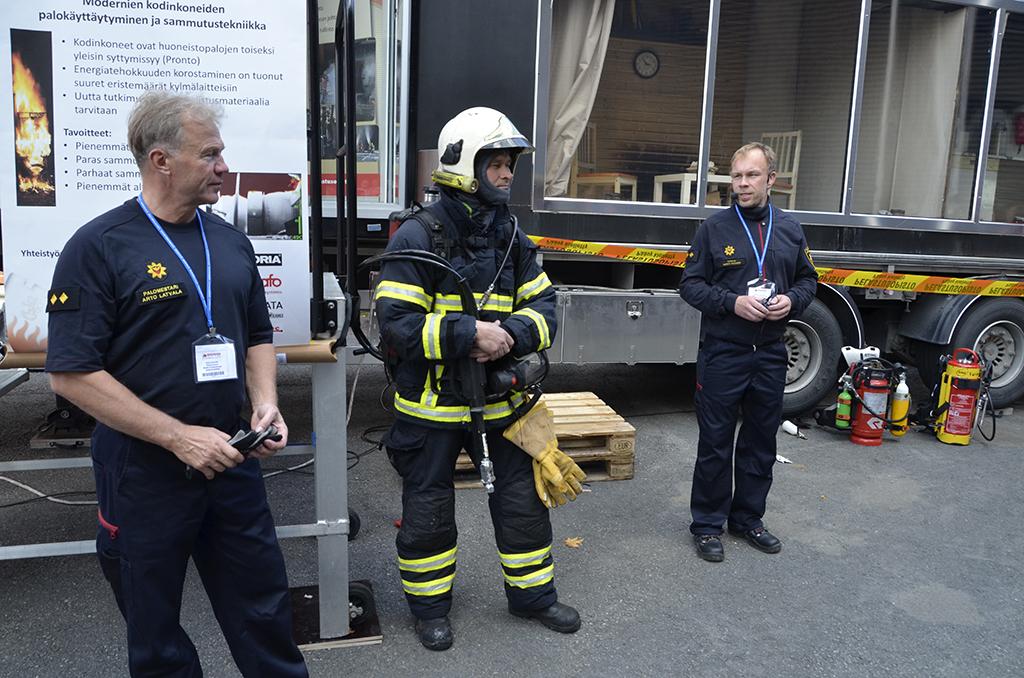 Palomestari Arto Latvala, yliopettaja Ismo Huttu ja tutkija Marko Hassinen demonstroivat turvallisuusmessuilla kodinkoneiden tulipaloja.