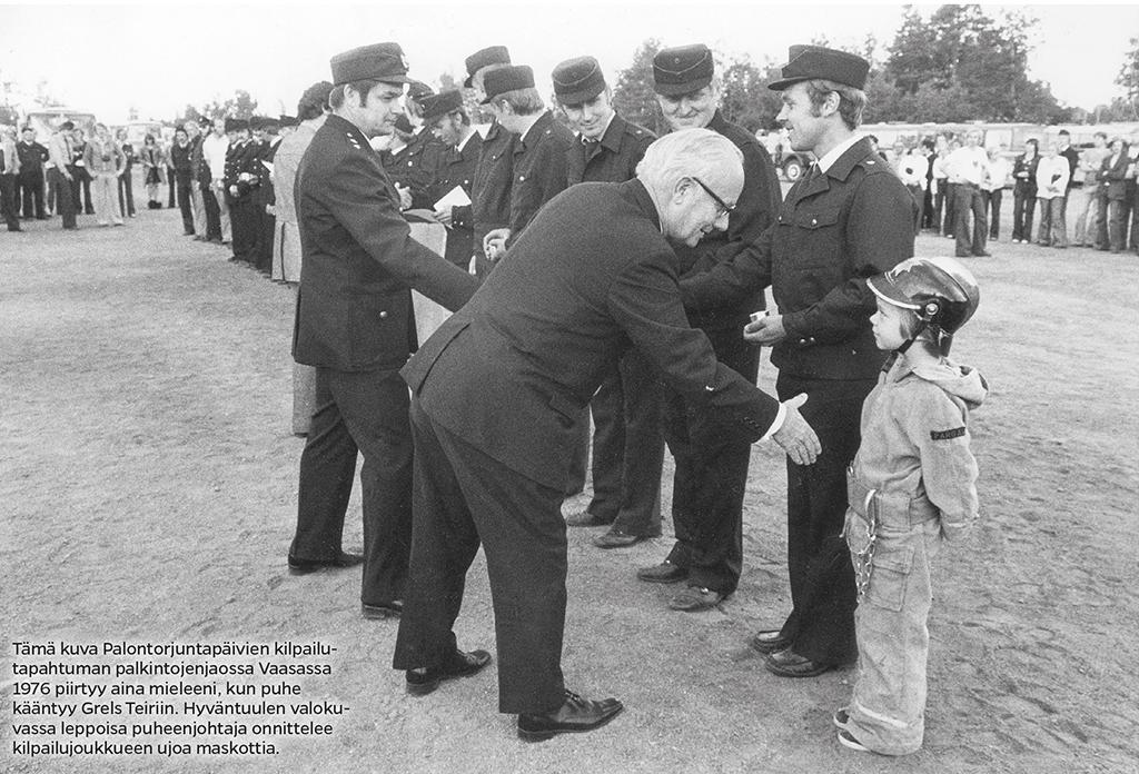 Kansanedustaja Grels Teir kättelee kuusivuotiasta Marko Laaksoa palkintojenjaossa.