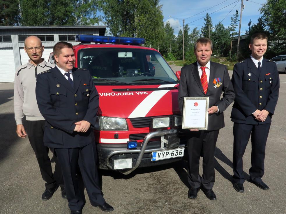 Entinen palokunnan päällikkö Markku Nokka (vas.), palokunnan päällikkö Toni Puhakka, puheenjohtaja Esa Mässeli ja varapäällikkö Mikko Seppälä iloisina arvonimestä.