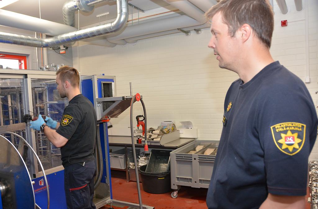 Palomies Juho Männistö pesee sammutusletkuja. Palopäällikkö Sampsa Lintunen pitää hyvänä, että työaikajärjestelyistä on sovittu hyvässä hengessä henkilöstön kanssa.