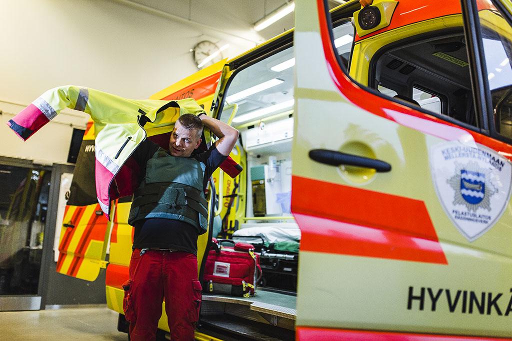 Ensihoitaja Ville Lindroth pukee päälleen viiltosuojaliiviä Hyvinkään asemalla vuonna 2018. Arkistokuva.