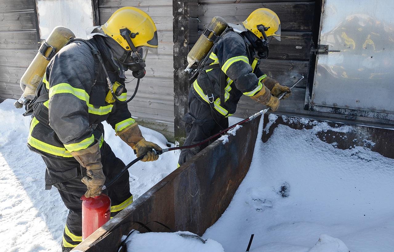 Kodinkonepalo sammui tehokkaasti Pelastusopiston harjoitusalueella hirsitalon seinän läpi viedyn pistosuihkuputken avulla.