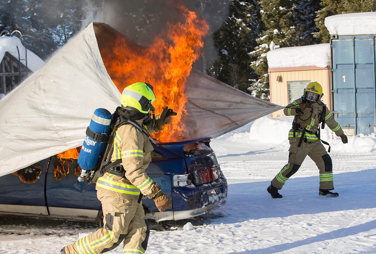 Isolla autonsammutuspeitteellä palo saadaan nopeasti hallintaan. Kuva on otettu Lapin pelastuslaitoksen Rovaniemen harjoitusalueella. Testissä on vesivaleltava sammutuspeite.