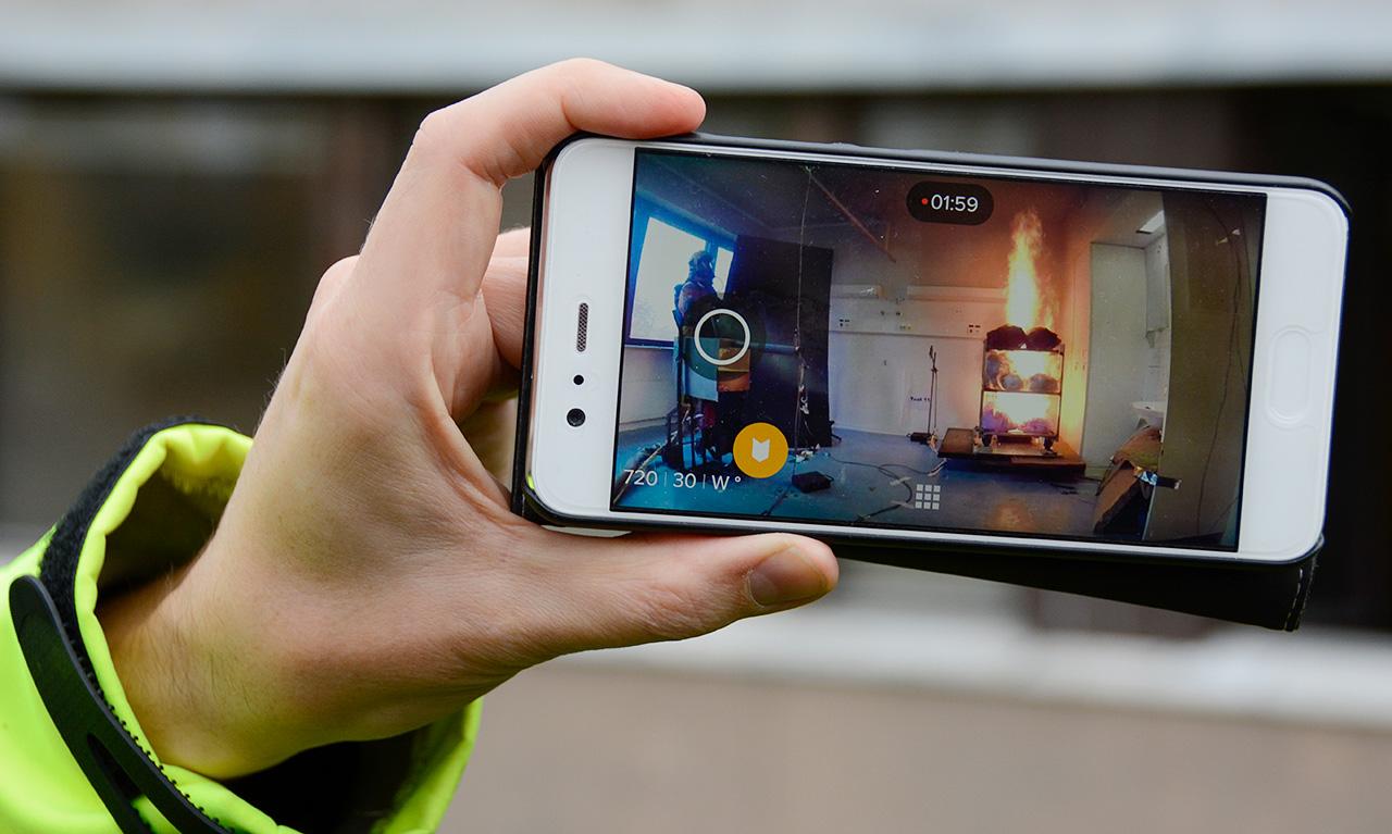 Palomies Juha Salonen havainnoi huoneessa viidettä koepolttoaan tulipalon kehittyessä. Tarkkailijat seurasivat palokoetta Sysmän vanhan terveyskeskuksen takapihalla kännykän näytöltä.