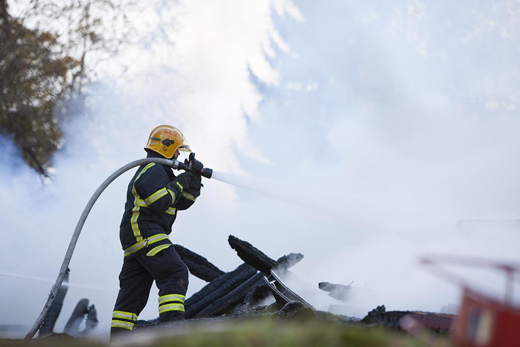 Palomies sammuttamassa Joensuun Kiihtelysvaaran kirkkoa tuhopolton jälkeen syyskuussa 2018.