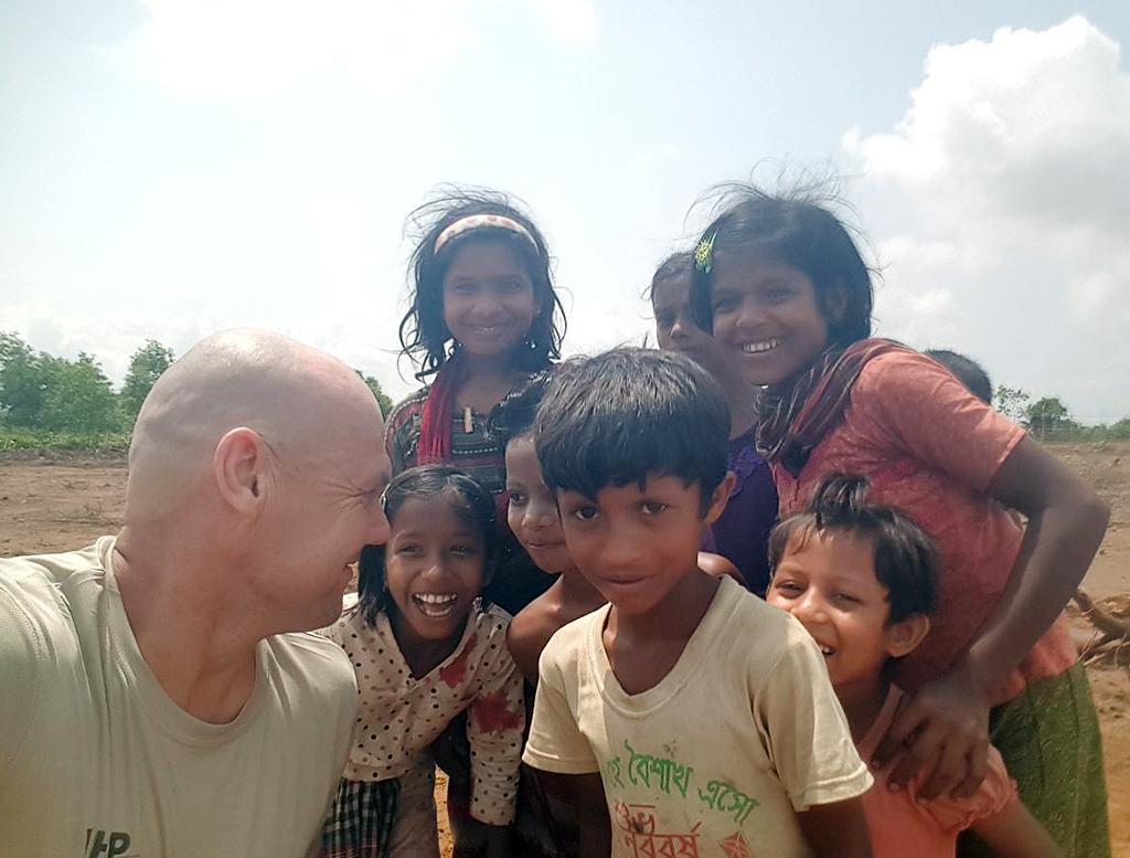 Leiriteknikko Jari Tarvus paikallisten lasten kanssa leirin rakennusvaiheen alussa Myanmarin rajalla vuonna 2018.