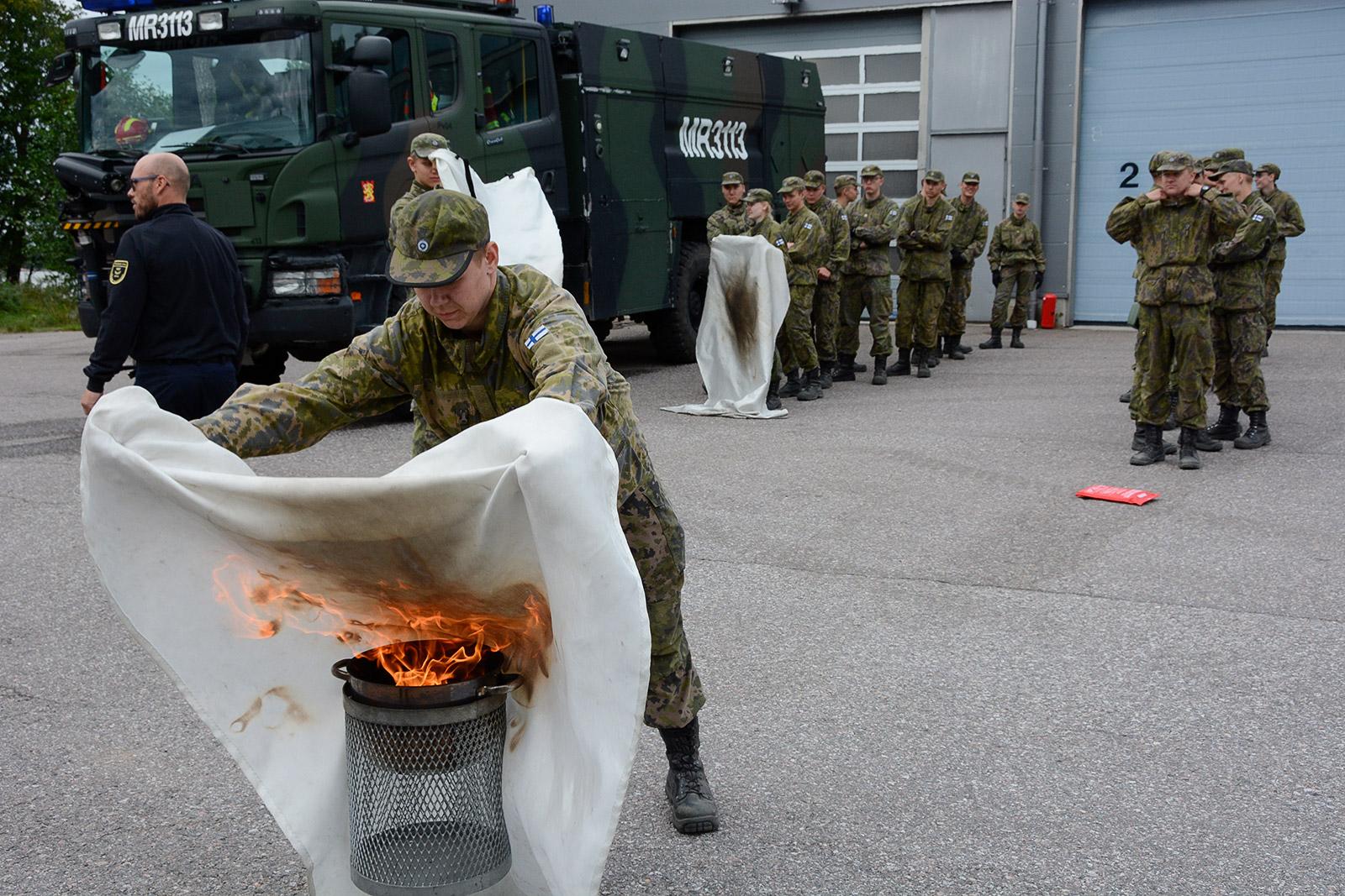 Kaartin jääkärirykmentissä Santahaminassa alkusammutustaitoja oppimassa 1. sotilaspoliisikomppanian 1-joukkue. Sammutuspeitteen käyttö vaikutti olevan haastavin rasti.