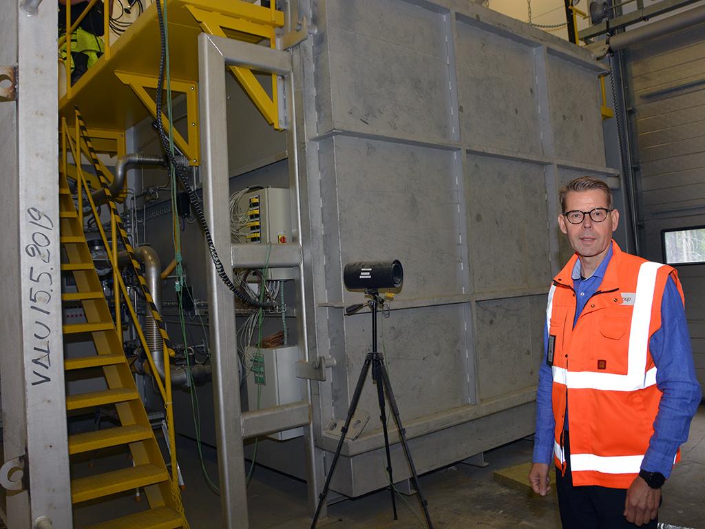 Tuotekehitysjohtaja Jari Hokkanen esittelee polttouunia, jossa testattavaa tuotetta poltetaan yli tuhannen asteen lämpötilassa.