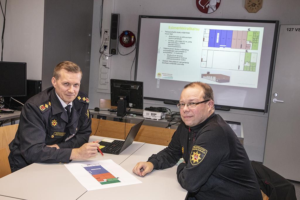 Pelastusjohtaja Markus Viitaniemi ja palopäällikkö Mika Viertola tarkastelevat uuden aseman mallia.
