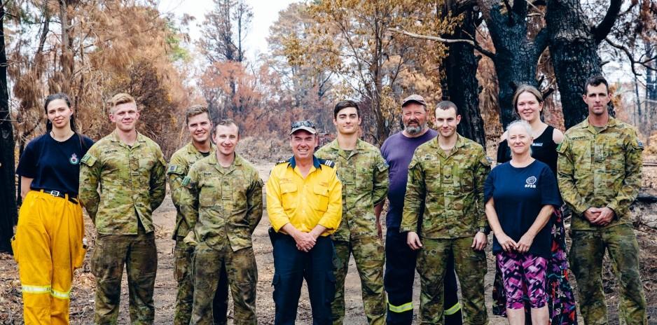 Kapteeeni O'Connor (keskellä keltaisessa asussa), palomiehet ja kylän raivaustöihin osallistuneet sotilaat.