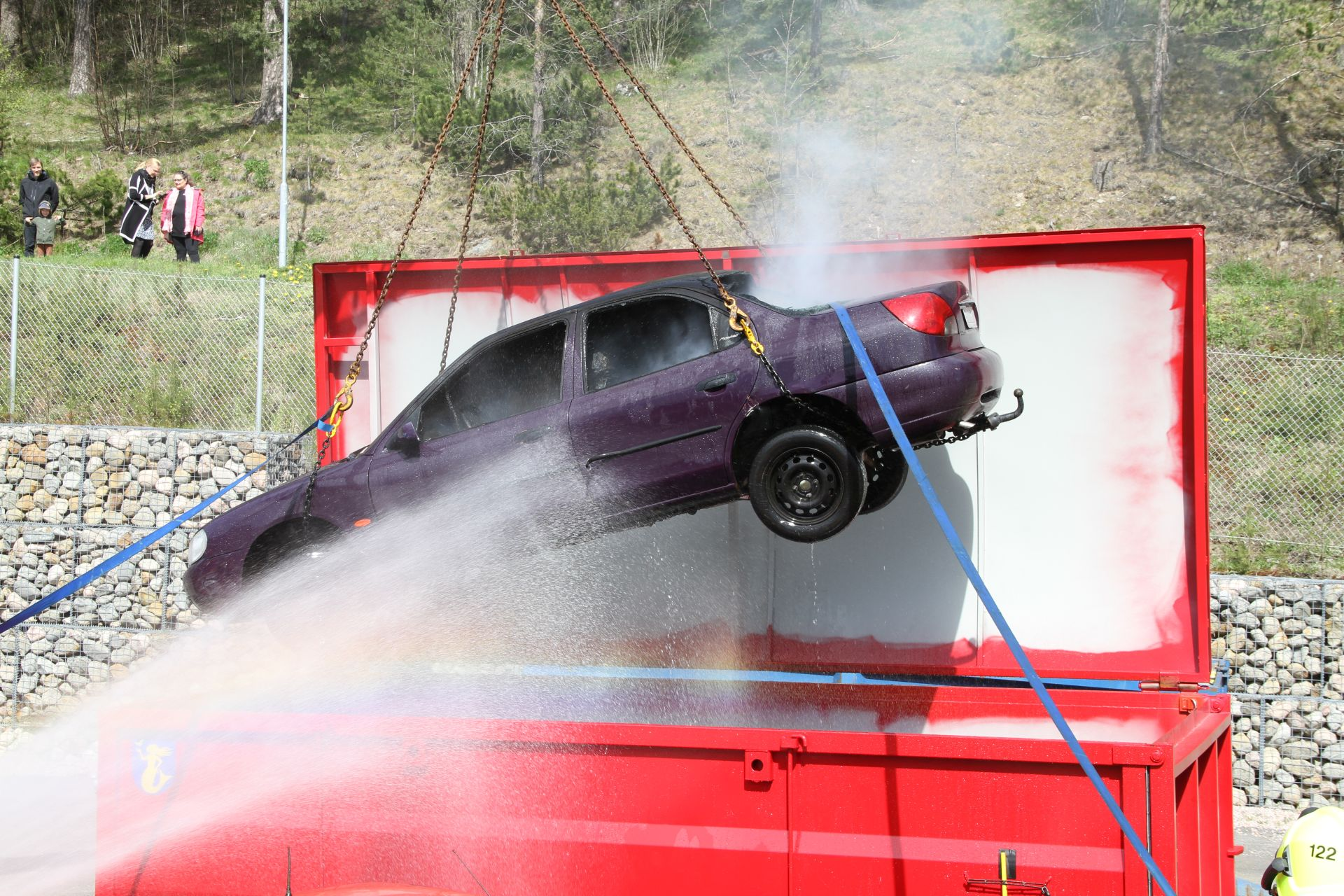 Päijät-Hämeen pelastuslaitos harjoittelemassa sähköauton akkupalon sammuttamista. Auto nostetaan kokonaisuudessaan konttiin vesijäähdytykseen. Kuva: Marko Nieminen / Päijät-Hämeen pelastuslaitos
