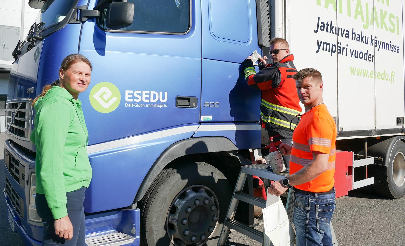 Kuvassa vasemmalla Esedun koulutuspäällikkö Kirsi Malmstedt, keskellä teippaamassa CTIF:n ISO 17840 -projektin suomalaisedustaja Mikko Saastamoinen ja oikealla Esedun liikenneopettaja Tuomas Tiusanen.