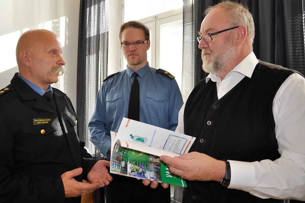 Matti Waitinen ojensi tekemänsä Vaaran paikka -kirjan professori Leif Åbergille. Taustalla tuolloin turvallisuusviestintäryhmän puheenjohtajana toiminut Jari Lepistö.