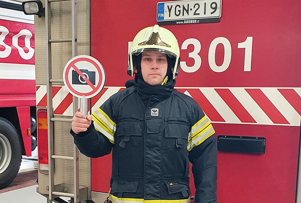 Ensihoitaja Jaakko Rinkinen pitelee kuvauskieltomerkkiä seisoessaan paloauton edustalla.