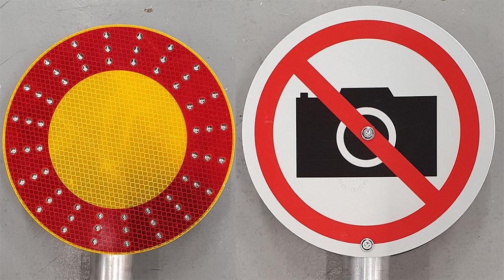 Käsiopastin, jonka toisella puolella on kuvaamisen kieltävä merkki.