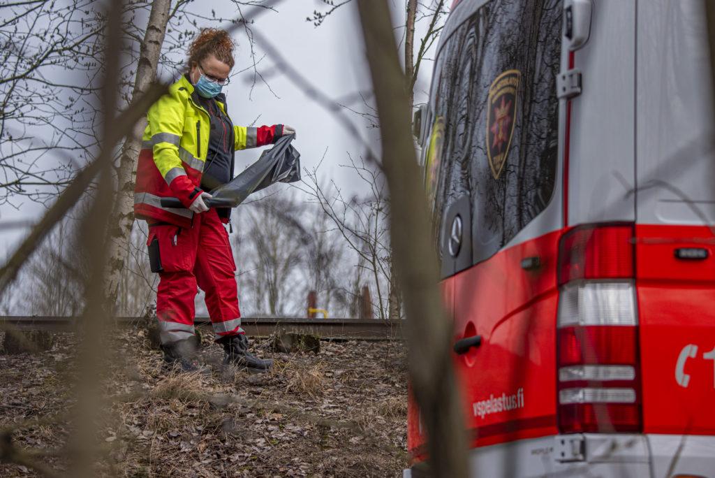 Ensihoitaja Sanna Virtanen junaradan vierellä jätesäkki kädessään.